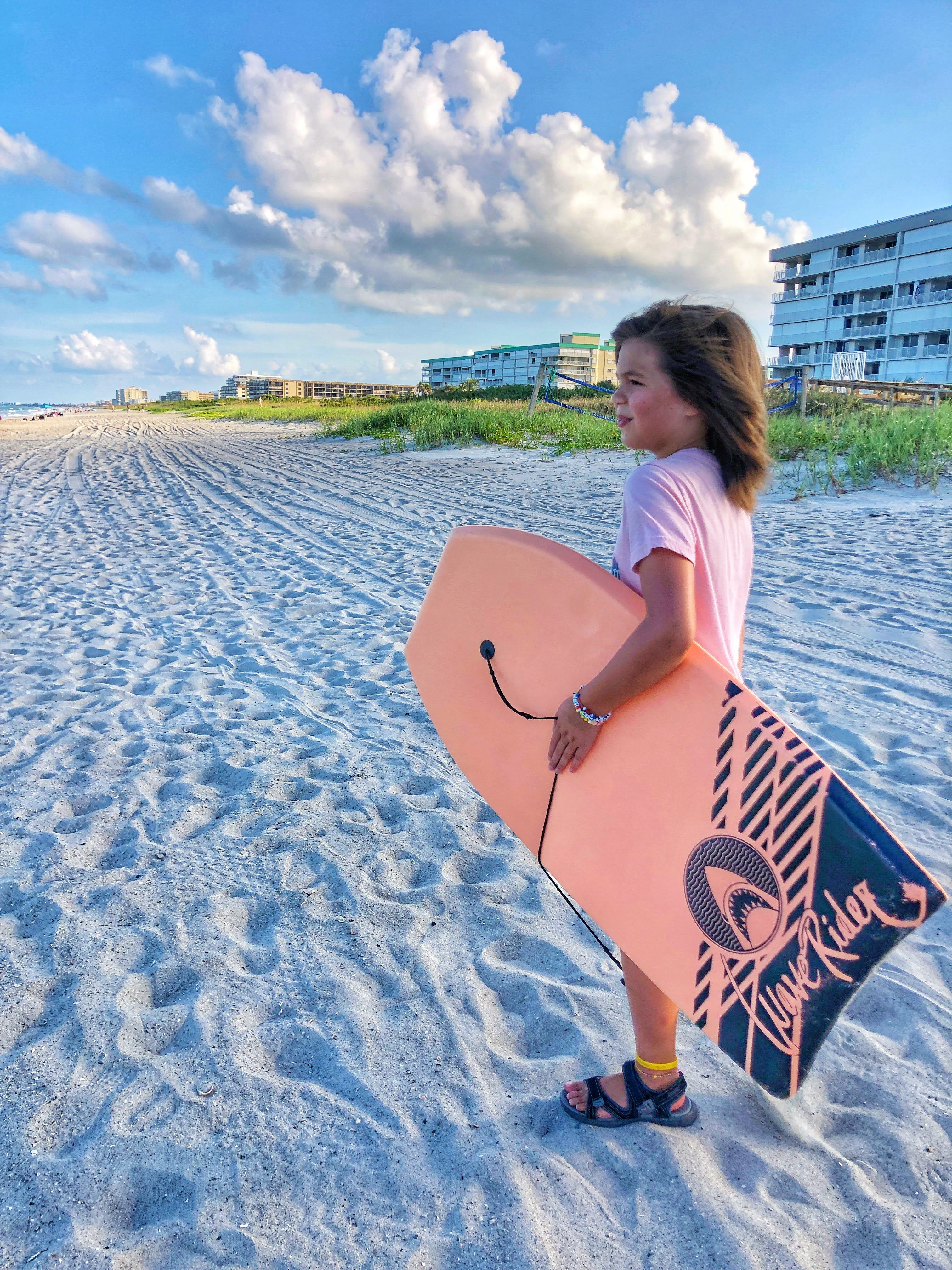 little girl with pink wakeboard on the beach with hotel behind her