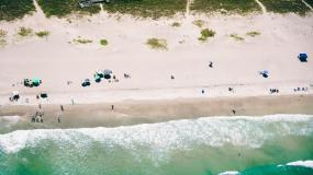 Arial view of the ocean waves breaking on the sandy shoreline.