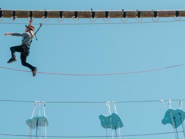 A man completing the challenge of the ropes course at Cocoa Beach Aerial Adventure