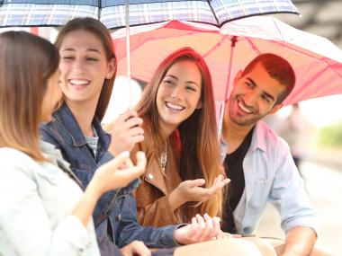 Four people chatting and smiling under umbrellas on a rainy day