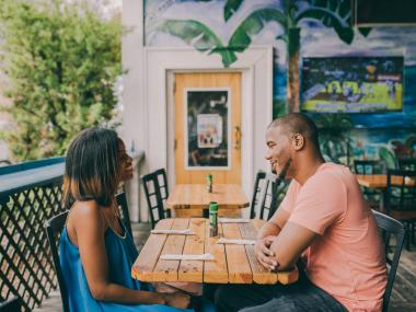 A couple has lunch on an outdoor patio in Cocoa Village