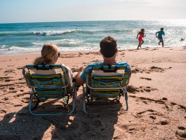 couple sits on the beach in chairs watching their 2 kids play in the water