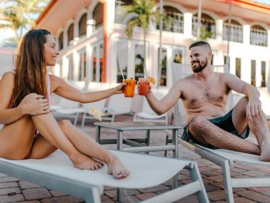Couple enjoying drinks by the pool