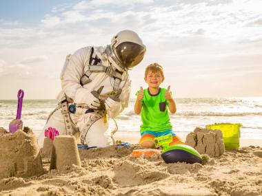 Starman and boy building sand castles on the beach