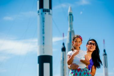A mother and daughter marvel at the rockets on display at the Rocket Garden at the Kennedy Space Center