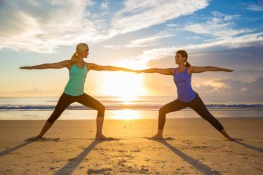 Two women doing yoga on the beach