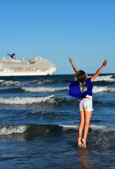 Young girl enjoys the beach at Jetty Park before her cruise vacation from Port Canaveral