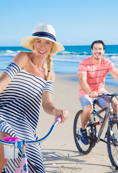 A woman and man riding bikes on the beach in Melbourne, FL