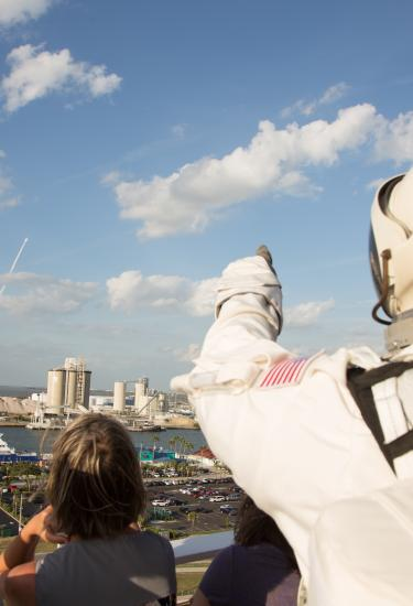 An astronaut watches a rocket launch from the viewing balcony at the Exploration Tower in Port Canaveral
