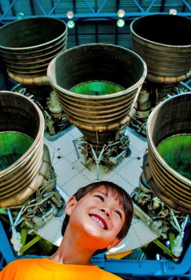 A kid smiling and having fun underneath the engine of a Saturn V rocket at Kennedy Space Center Visitor Complex in Titusville, FL