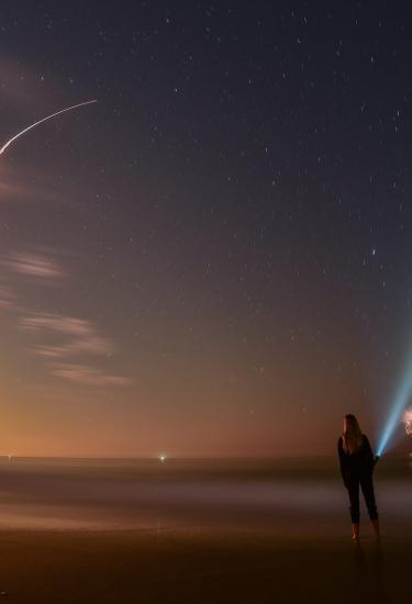 rocket is launching at dusk while a woman on the beach watches and flashes a flashlight into the sky
