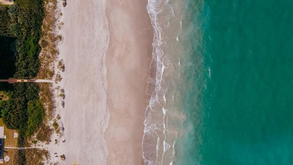 Aerial view of where the water meets the sand on the beach