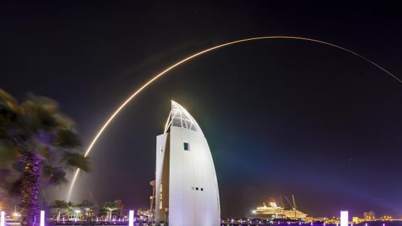 A nighttime rocket launch seen flying above the Exploration Tower in Port Canaveral