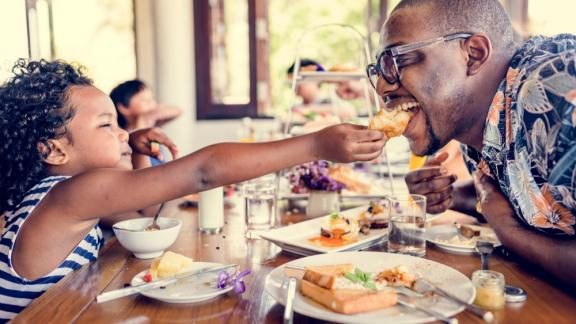 Daughter feeds dad a piece of food at brunch