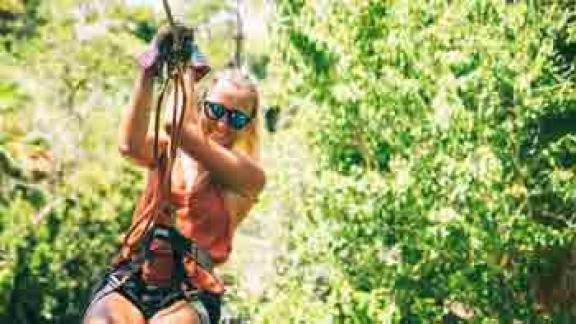 A woman zips down the zip-line at the Treetop Trek at the Brevard Zoo in Viera, FL