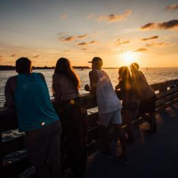 A group of millennials watches the sunrise over the ocean at Jetty Park in Port Canaveral