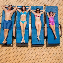 A family lounging on the deck of a cruise ship