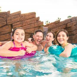 A family enjoying the hotel pool at the Radisson Resort at the Port before their cruise vacation from Port Canaveral