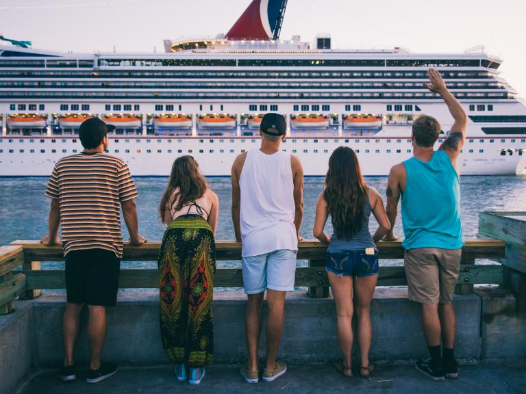 Millennials watch a cruise ship depart from Jetty Park in Port Canaveral