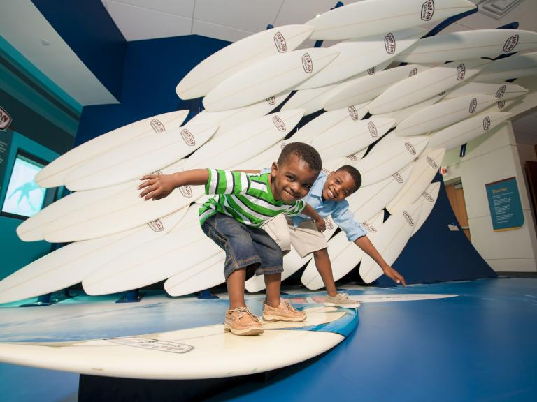 Kids playing at an interactive surfboard art display at the Exploration Tower in Port Canaveral