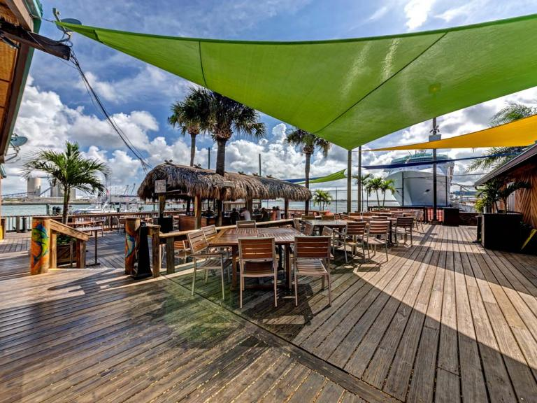 Outdoor patio with waterfront view at Grills Seafood Deck & Tiki Bar in Port Canaveral