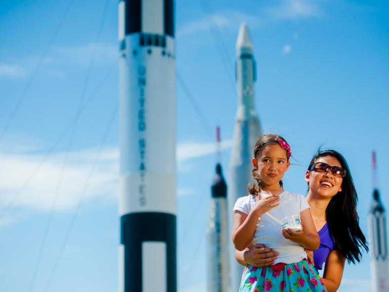 A mom and daughter gaze at the rockets on display in the Rocket Garden at Kennedy Space Center