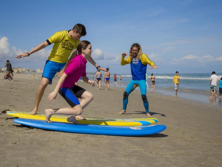 The Ron Jon Surf School teaching a brother and sister how to surf in Cocoa Beach, FL