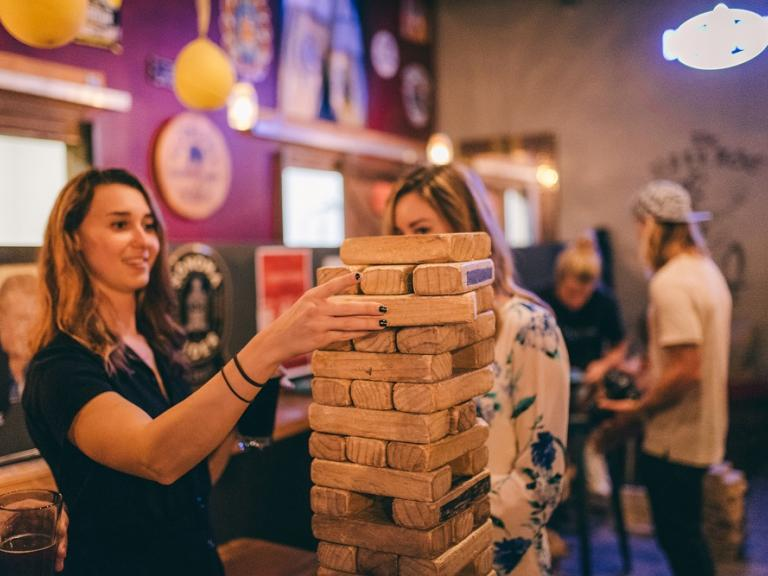 People playing giant jenga at the Village Idiot Pub in Cocoa Village