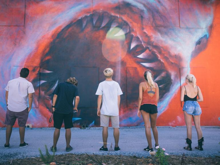 A group of friends gazes in wonder at the Shark Toof wall murals in the Eau Gallie Arts District