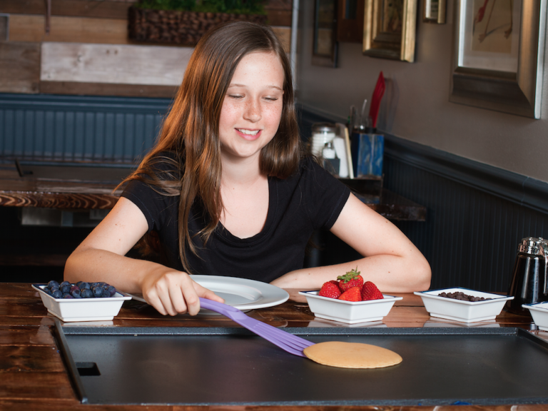 A young girl making her own pancake at the griddle-top table at Backwater in Downtown Melbourne, FL