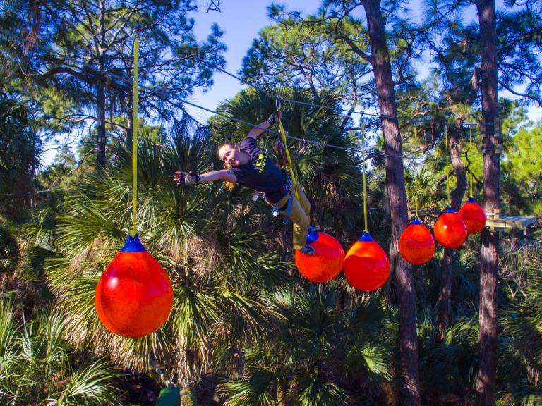 Hanging in the air navigating different obstacles at the Treetop Trek at the Brevard Zoo in Viera, FL