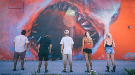 A group of people looking at the Shark Toof mural in the Eau Gallie Arts District
