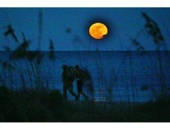 Moonrise over the Atlantic with two people seen through brush