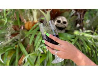 a hand with a glass of wine in the foreground with a skull in plants in the background