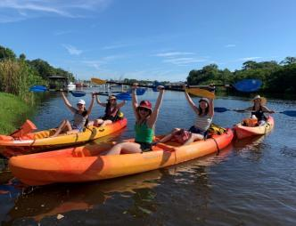 A group is kayaking on the Eau Gallie River on rented kayaks from Ballard Boards in Melbourne, FL