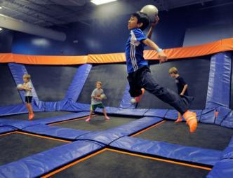 A kid going airborne in a game of dodge ball at Sky Zone Indoor Trampoline Park in Rockledge, FL