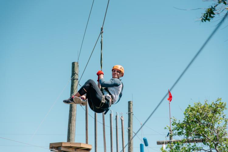 Zip-lining high above the ground at Cocoa Beach Aerial Adventure