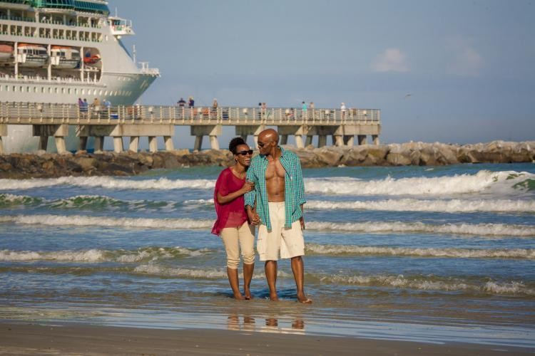Couple walking on the beach at Jetty Park with cruise ship sailing behind them